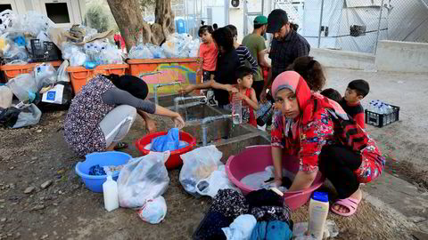 Migrants wash their clothes and fill bottles with water at a makeshift camp next to the Moria camp for refugees and migrants on the island of Lesbos, Greece, September 18, 2018. Picture taken September 18, 2018. REUTERS/Giorgos Moutafis ---