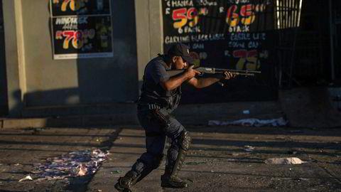 En sørafrikansk politimann skyter gummikuler for å stoppe plyndrere under sist ukes opptøyer i Mahikeng i Nordvest-provinsen i Sør-Afrika.