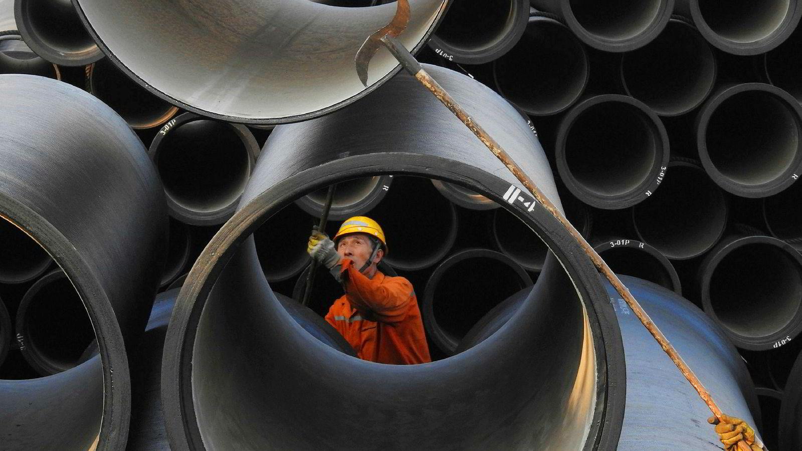 Verdensøkonomien går for full maskin. Både USA, Europa og Kina har solid økonomisk vekst – samtidig, for første gang siden 2008. En arbeider tar imot rør på havnen i Lianyungang i Kina.
