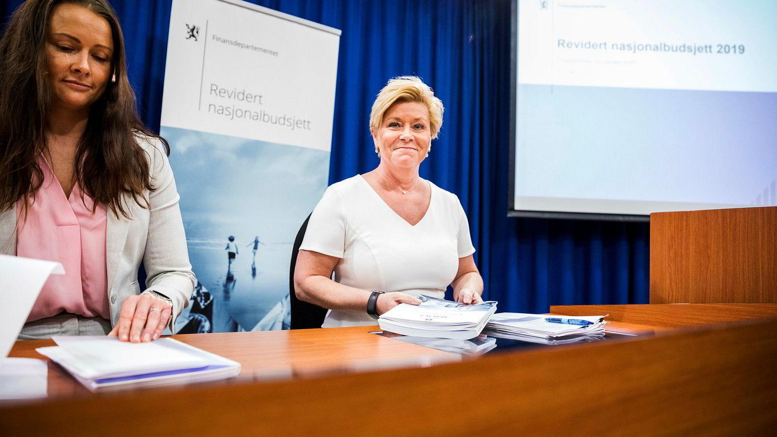 Siv Jensen (til høyre) under pressekonferansen om revidert nasjonalbudsjett 2019. Her sammen med kommunikasjonssjef Therese Riiser Wålen.