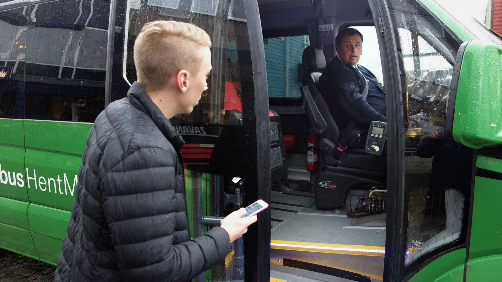 Kollektivselskapet Kolumbus tester nå ut en «hent-meg-buss» i Sauda. Den har ingen faste ruter, men baserer seg på folks løpende bestillinger. Den Vancouver-baserte utvikleren Kristoffer Vik Hansen viser sin bestilling til sjåfør Tor Michaelsen.