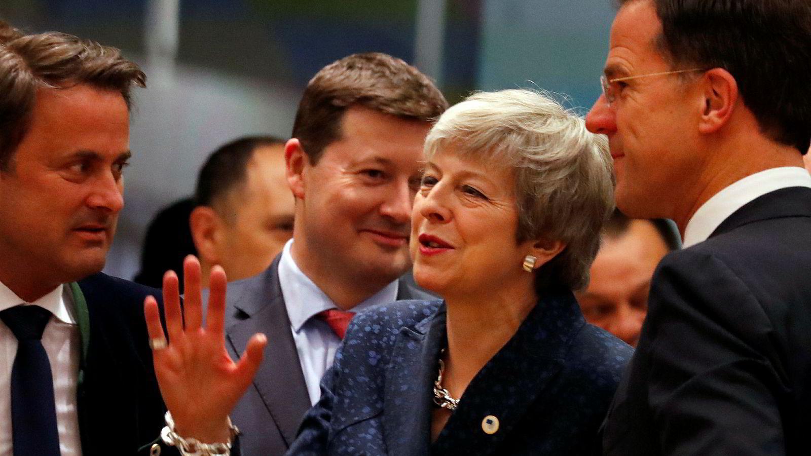 Statsminister Theresa May ble omringet av den nederlandske statsministeren Mark Rutte (til høyre) og Luxembourgs statsminister Xavier Bettel (til venstre) under toppmøtet torsdag.
