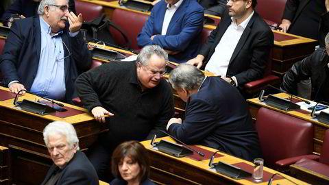 Den tidligere greske utenriksministeren Nikos Kotzias snakker med tidligere visestatsminister og finansminister Evangelos Venizelos under en debatt i det greske parlamentet fredag.