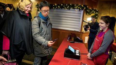 Vipps' internasjonale direktør Berit Svendsen følger med når forretningsutvikler Ruimin Yang demonstrerer mobilbetaling i kassen – delvis ved hjelp av Vipps' teknologi og infrastruktur. Vertinne Helene Karlsen i Pepperkakebyen i Bergen får bekreftet betalingen nesten umiddelbart.