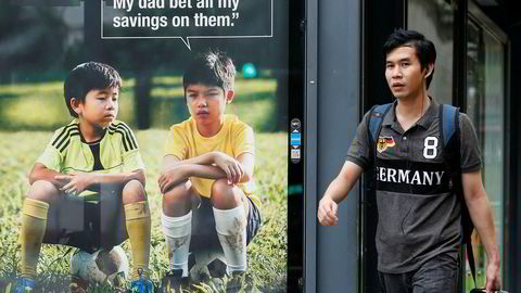Antallet spillavhengige har ligget stabilt de ti siste årene, til tross for at spillreklamemarkedet har gått fra nesten null til en halv milliard kroner. Her går en mann forbi reklame for spill i Singapore.