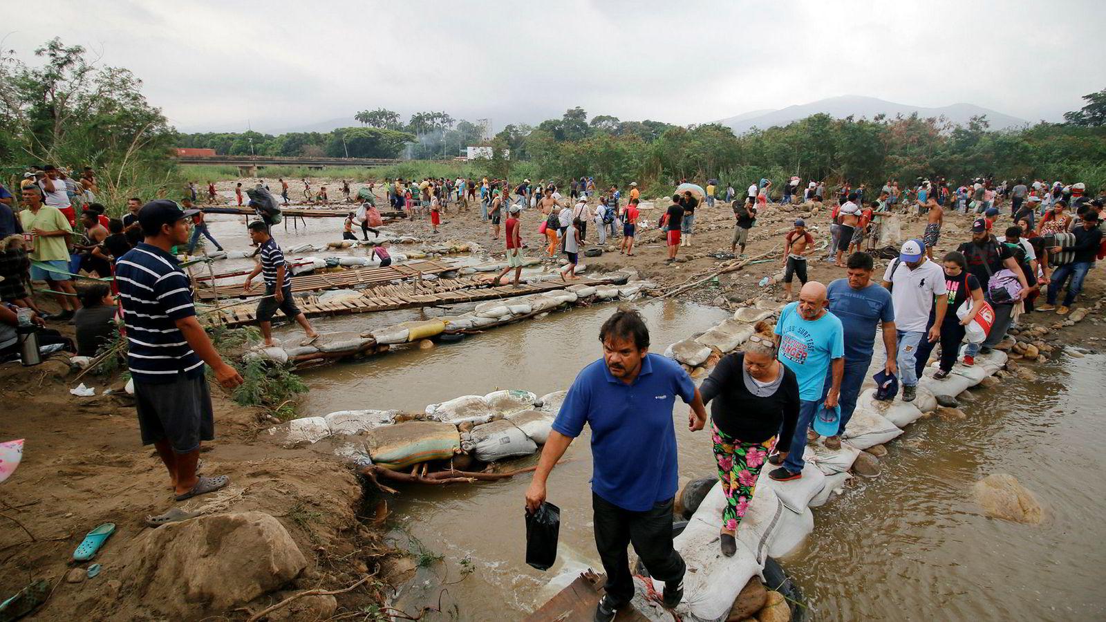 Folk fra Venezuela krysser elven Tachira og inn i Colombia.