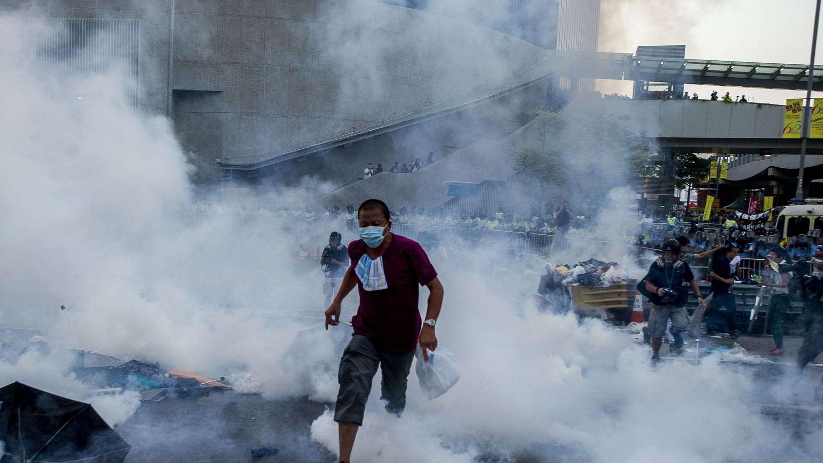 Politiet brukte søndag tåregass mot demonstrantene i Hong Kong. Foto:  AFP PHOTO / XAUME OLLEROS/NTB SCANPIX.
