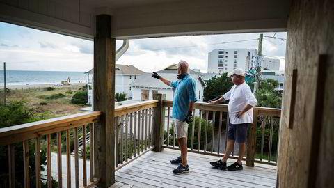 Phil Gillespie (til venstre) og Neil Hyman ser fra terrassen at livvakttårnene på stranden blir demontert. Selv har de har dekket til alle vinduene og skal snart reise.