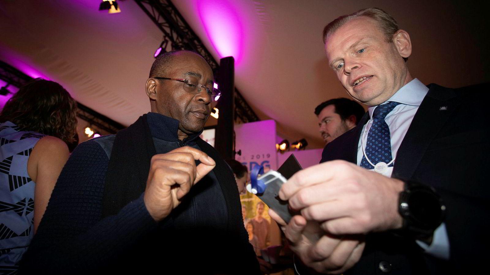 Til mobilmilliardær og Afrikafilantrop Strive Masiyiwa viser Yara-sjef Svein Tore Holsether frem en Yara-utviklet mobil-dings som kan brukes av bønder til å bestemme gjødselbehovet.