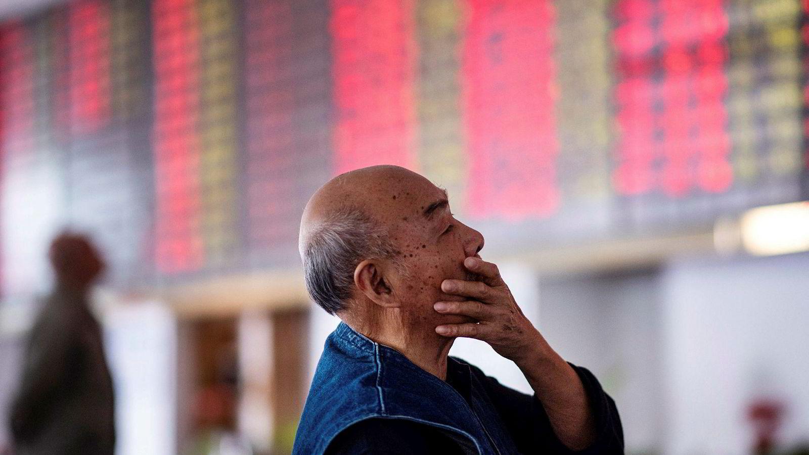 En kinesisk investor ser opp på de elektroniske tavlene som viser børsutviklingen i et meglerhus i Shanghai tidligere i høst.