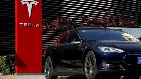 Rapport spår at Tesla vil miste lederposisjonen blant verdens produsenter av elbiler. FILE PHOTO: A Tesla car charges at a charging station in Beijing, China, April 18, 2017. REUTERS/Thomas Peter/File Photo Foto: Thomas Peter/Reuters/NTB Scanpix