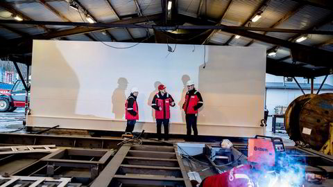 Et nytt understell til Vard-verftets battericontainer sveises sammen. I bakgrunnen produktansvarlig Kay Henning Higraff (til venstre), direktør Willie Wagen i Corvus Energy og Bjarte Sandnes, ansvarlig for innkjøp og logistikk i Vard Electro.