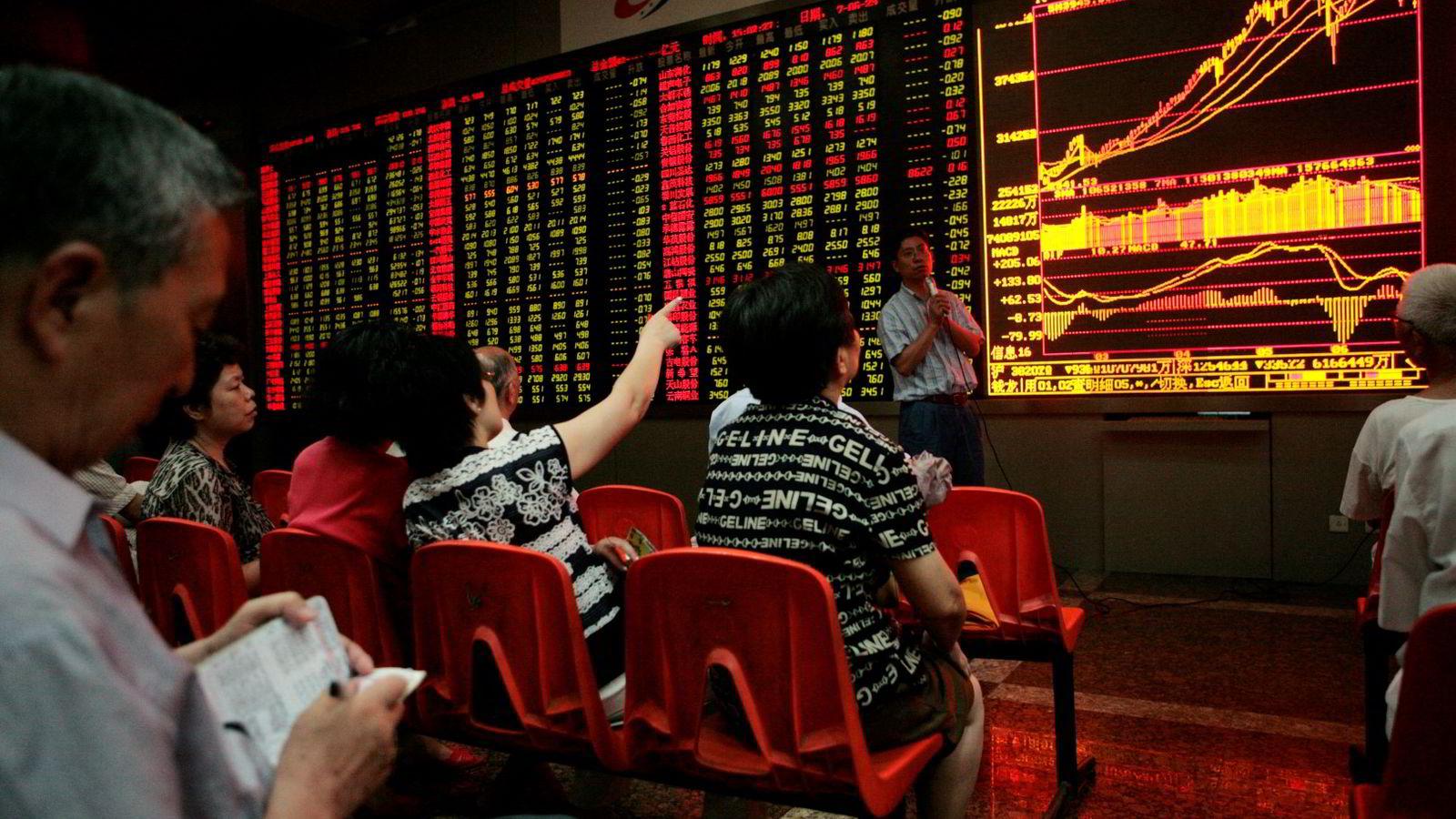 Folk studerer aksjekursene på Shanghai-børsen. Illustrasjonsfoto: Kevin Lee/