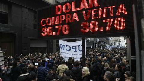 Statsansatte protesterer i Buenos Aires mot planlagte nedskjæringer og nedbemanninger, under et skilt som viser at valutaen peso har mistet halvparten av verdien mot dollar så langt i år.