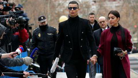 Fotballspilleren Cristiano Ronaldo ankommer retten sammen med sin spanske kjæreste Georgina Rodriguez i Madrid tirsdag.