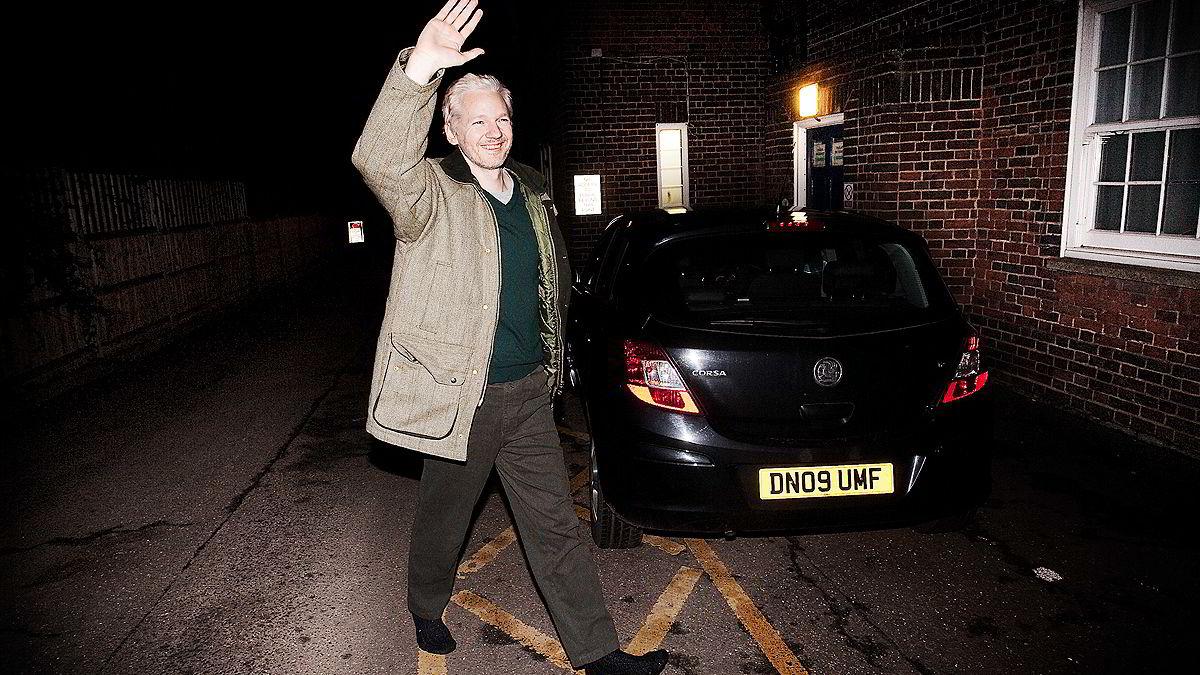 Julian Assange kom 25 minutter for sent til politistasjonen i Beccles. Selv uten sko hilste han helhjertet til en liten håndfull fans som ventet på ham.