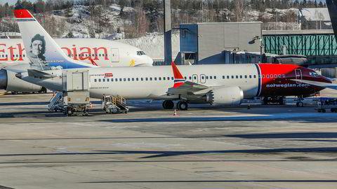 Et Boeing 737 MAX 8 fly fra Norwegian står ved gaten på Oslo lufthavn. Bak står et Boeing 777-260 (ET-ANP) fra Ethiopian Airlines.