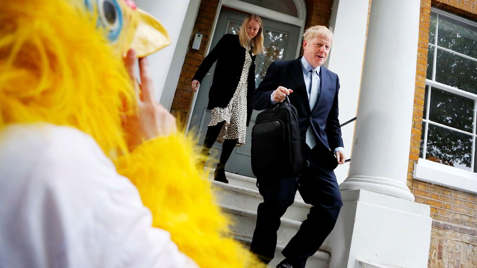 A person dressed as a chicken stands outside as British Conservative Party lawmaker Boris Johnson leaves his home in London, Thursday, June 13, 2019. Boris Johnson, who ran London as mayor for eight years until 2016 and then became Britain's foreign secretary until his resignation last summer, is a confident if erratic Conservative Party star with a simple message: I'll sort out Brexit. (AP Photo/Frank Augstein) ---