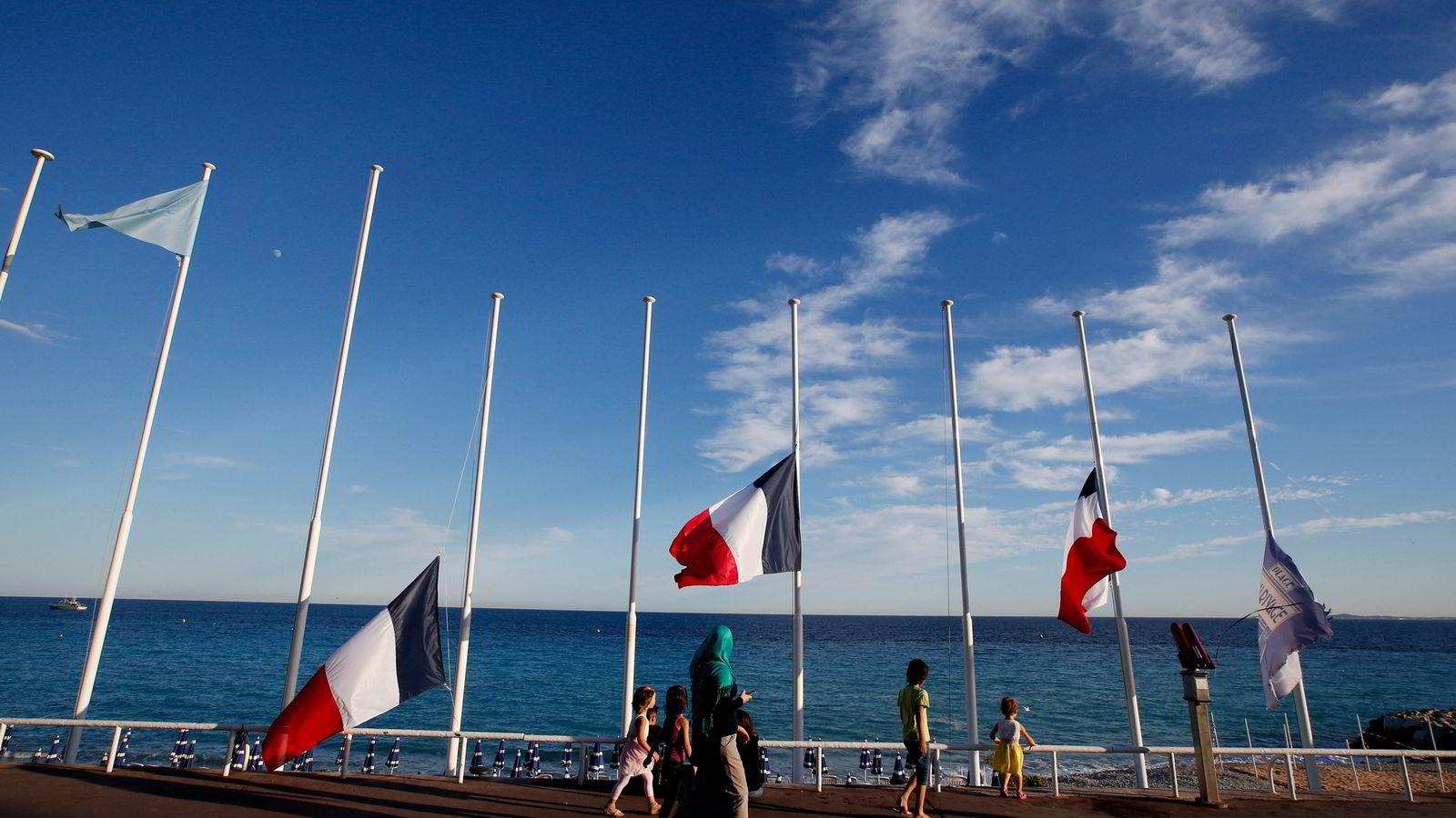 Flaggene vaiet på halv stang til minne om ofrene etter tragedien i Nice. Foto: Eric Gaillard/Reuters/NTB Scanpix