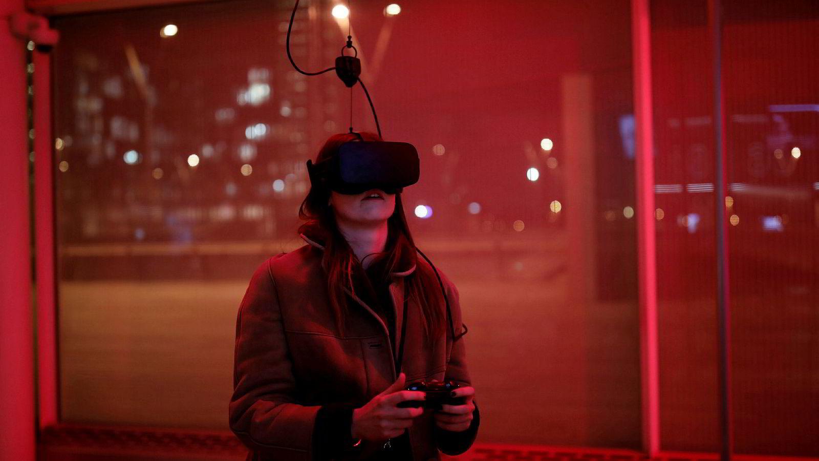 Oculus er dømt til å betale erstatning for å ha benyttet stjålet datateknologi. På bildet spiller en kvinne videospill med Oculus Rift VR-briller.