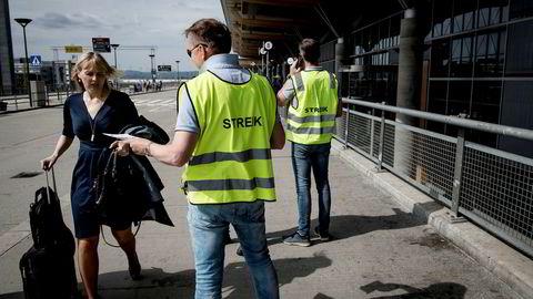 Streikevaktene Runar Østby (i midten) og Øystein Syrist (til høyre) deler ut løpesedler ved Oslo lufthavn Gardermoen tirsdag. Ingen av pilotene ville snakke med mediene.