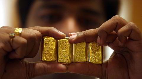 Gull er en av favoritt-investeringene blant indiske husholdninger. Nå kan Indere kan snart sette kullet sitt i banken og få renter på samme måte som vanlige bankinnskudd. Her viser en selger frem gullbarrer i en butikk i Hyderabad i India. Foto: Krishnendu Halder/Reuters/NTB scanpix