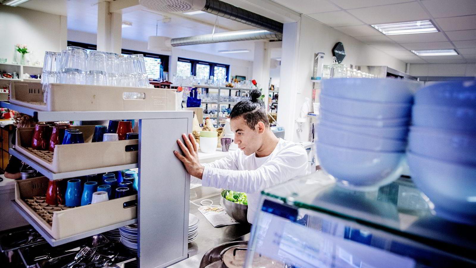 Arbeidsledige Michael Douglas Søraas (22) jobber på kjøkkenet på kafeen til Kirkens Bymisjon i Drammen, etter å ha blitt sendt hit av Nav som et vilkår for å få stønad til livsopphold. Foto: Fredrik Bjerknes