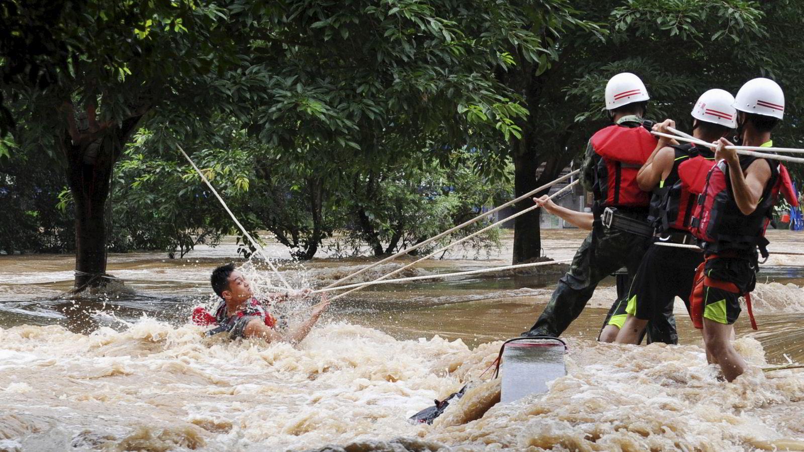 Havnivået i verden stiger i stadig raskere takt. På bildet hjelper redningsmannskaper en mann som er fanget av vannmassene etter at vannivået i elven Lijiang i Kina plutselig steg kraftig.