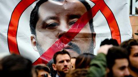Demonstranter holder en plakat med bilde av Matteo Salvini, leder av partiet Ligaen, mens de protesterer under ministerens besøk til Napoli denne uken.