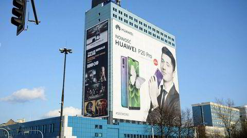 En reklame for Huawei der et bilde av fotballstjernen Robert Lewandowski som holder en smarttelefon dekker en halv bygning i Warszawa.