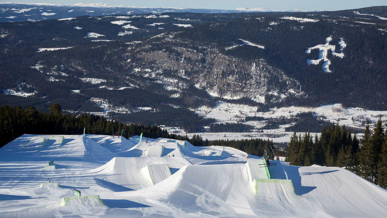 Med utsikt til fakkelmannen setter juniorlandslagets Tora Johansen skiene på tvers og sklir over en rail i Hafjells mest krevende terrengpark.