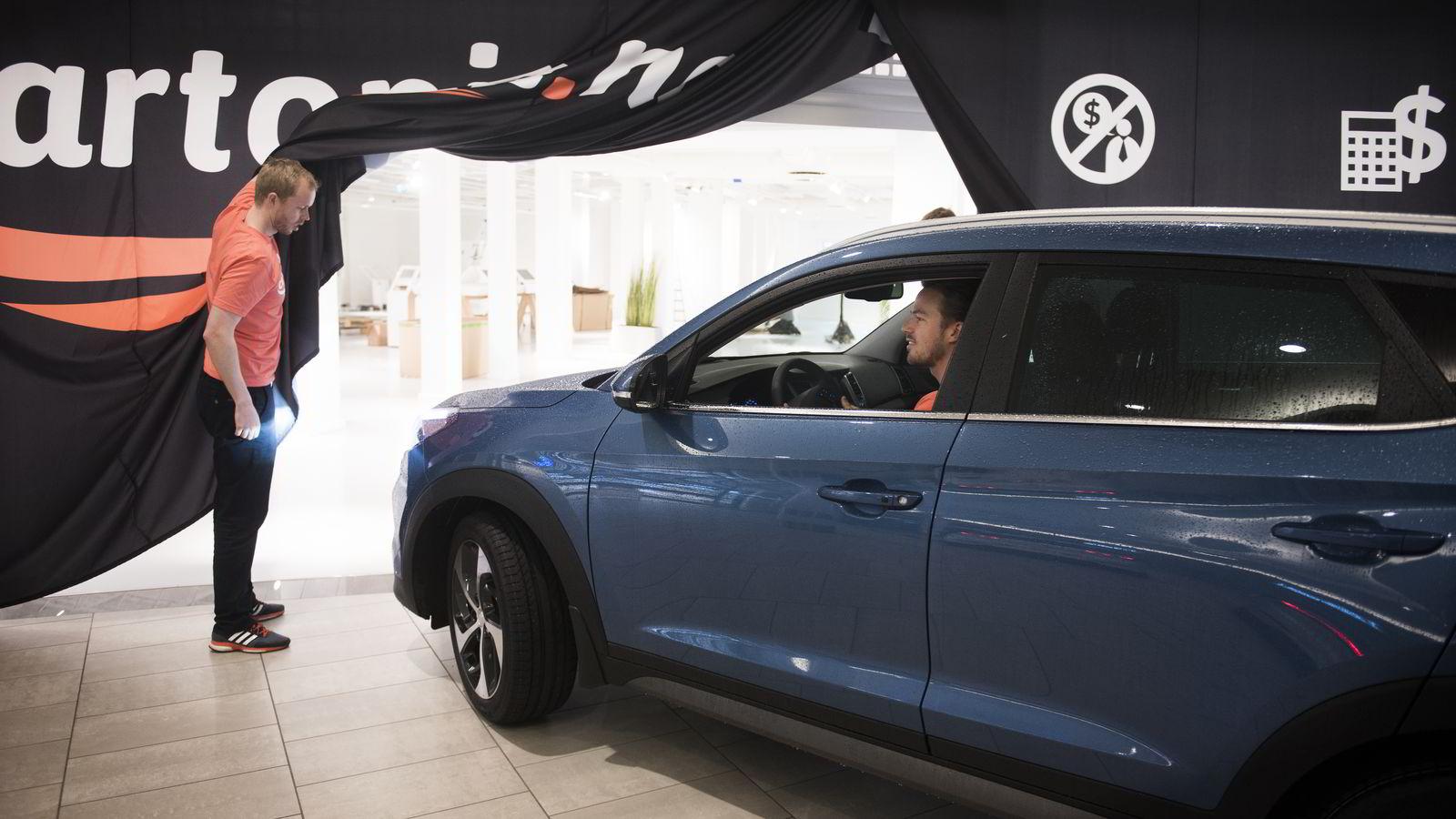 Vigbjørn Hassel Vaage holder opp gardinen, så fetteren Vemund Hassel får kjørt på plass den første bilen i lokalene på kjøpesenteret i Drammen.