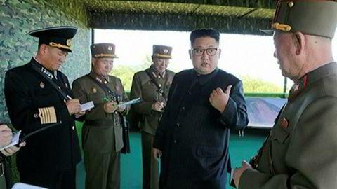 Nord-Koreas diktator, Kim Jong-un poserer sammen med militære. Han har bidratt til å øke spenningen betraktelig med en ny rakett som passerte over Japan.