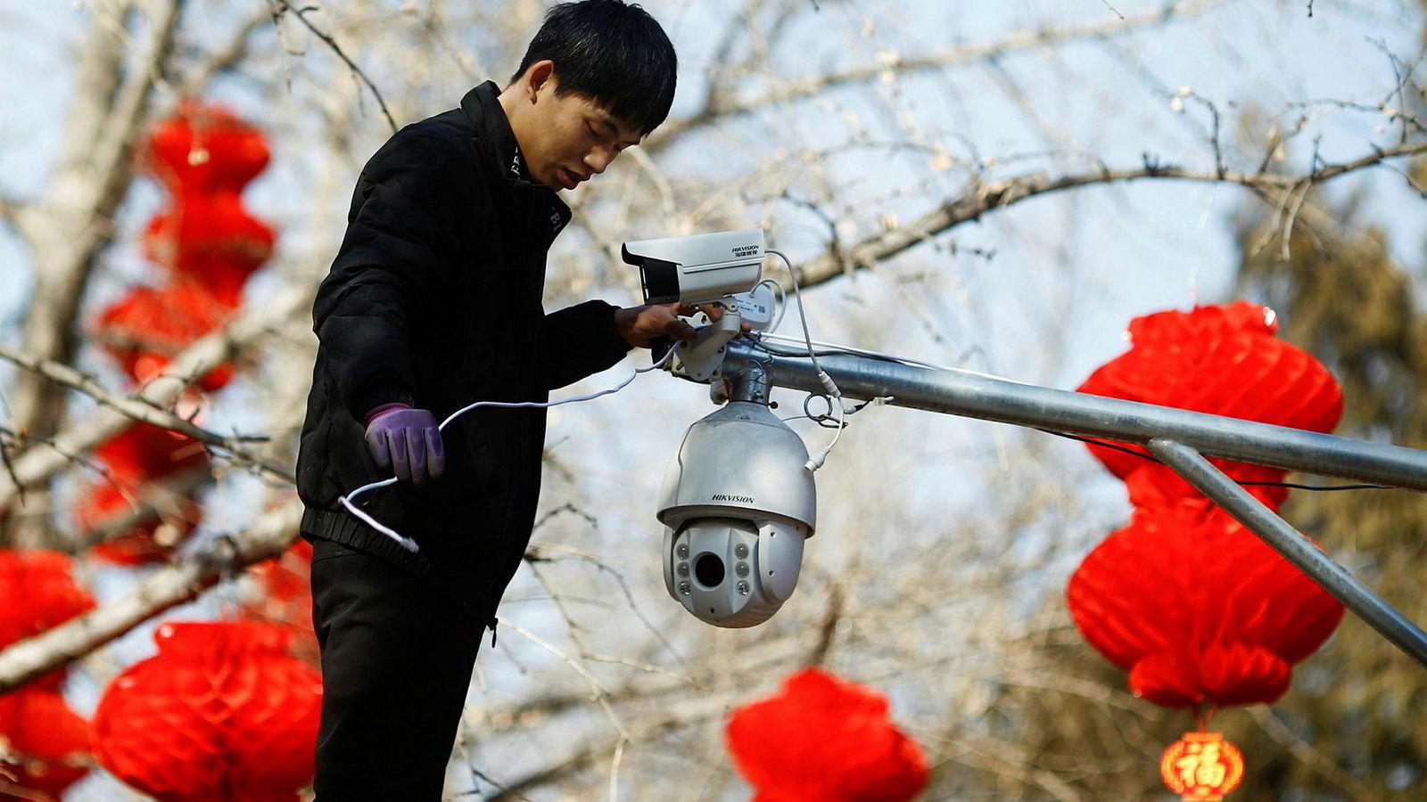En arbeider setter opp overvåkningskameraer fra Hikvision i Beijing i anledning av den kinesiske nyttårsfeiringen i februar. Artikkelforfatterne bruker Oljefondets investering i Hikvision som et eksempel på de vanskelige etiske dilemmaene fondet står overfor.