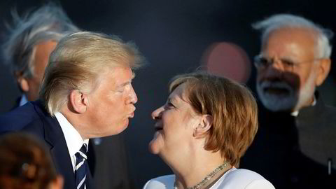 President Donald Trump og Tysklands statsminister Angela Merkel møttes under G7-ledernes fotoseanse søndag. Mandag skal de diskutere Iran og andre spørsmål på tomannshånd.