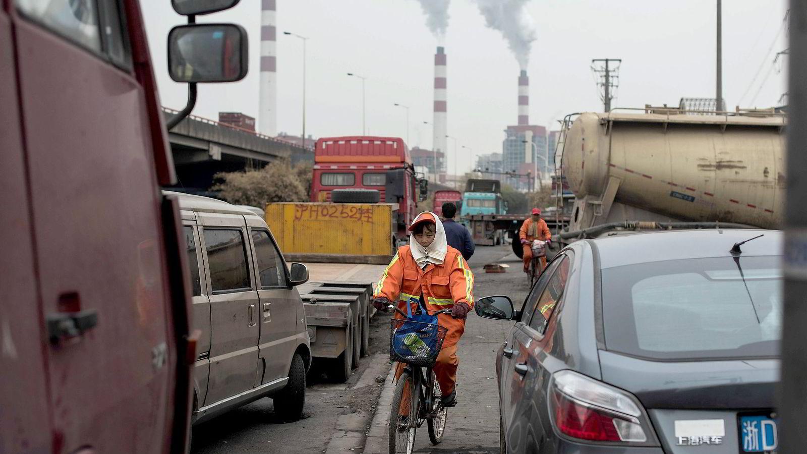 I 2014 annonserte Kinas president at Kina skal nå utslippstoppen omtrent i 2030. Her sykler en kvinne med det kulldrevne Shanghai Waigaoqiao-kraftverket i bakgrunnen. Foto: Johannes Eisele/AFP/NTB Scanpix