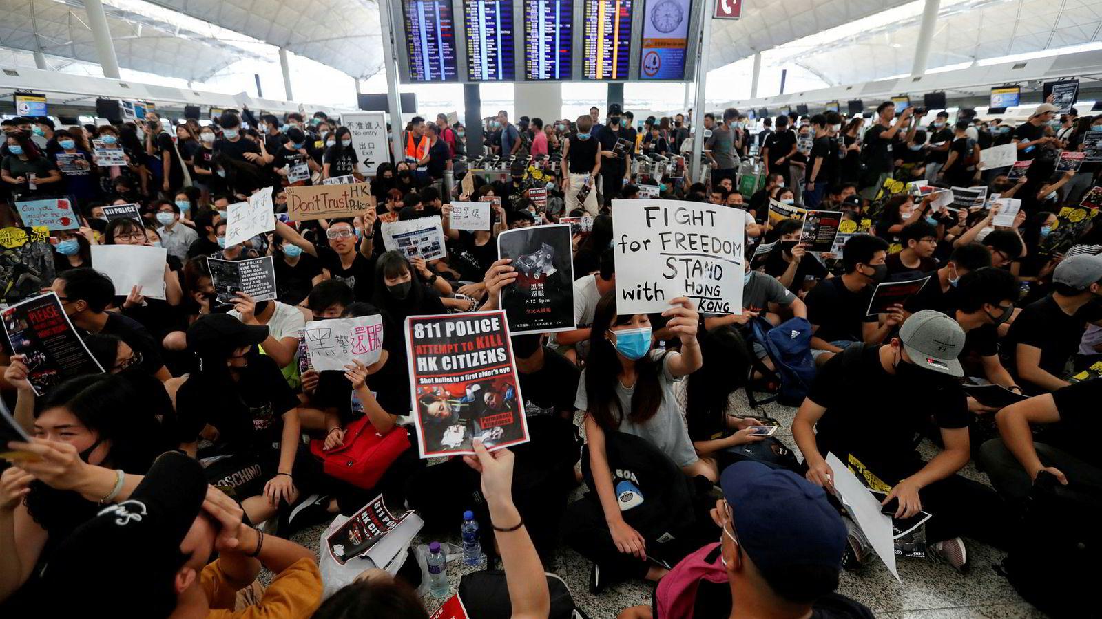 Et stort antall demonstranter blokkerer avgangshallen ved flyplassen i Hongkong mandag.