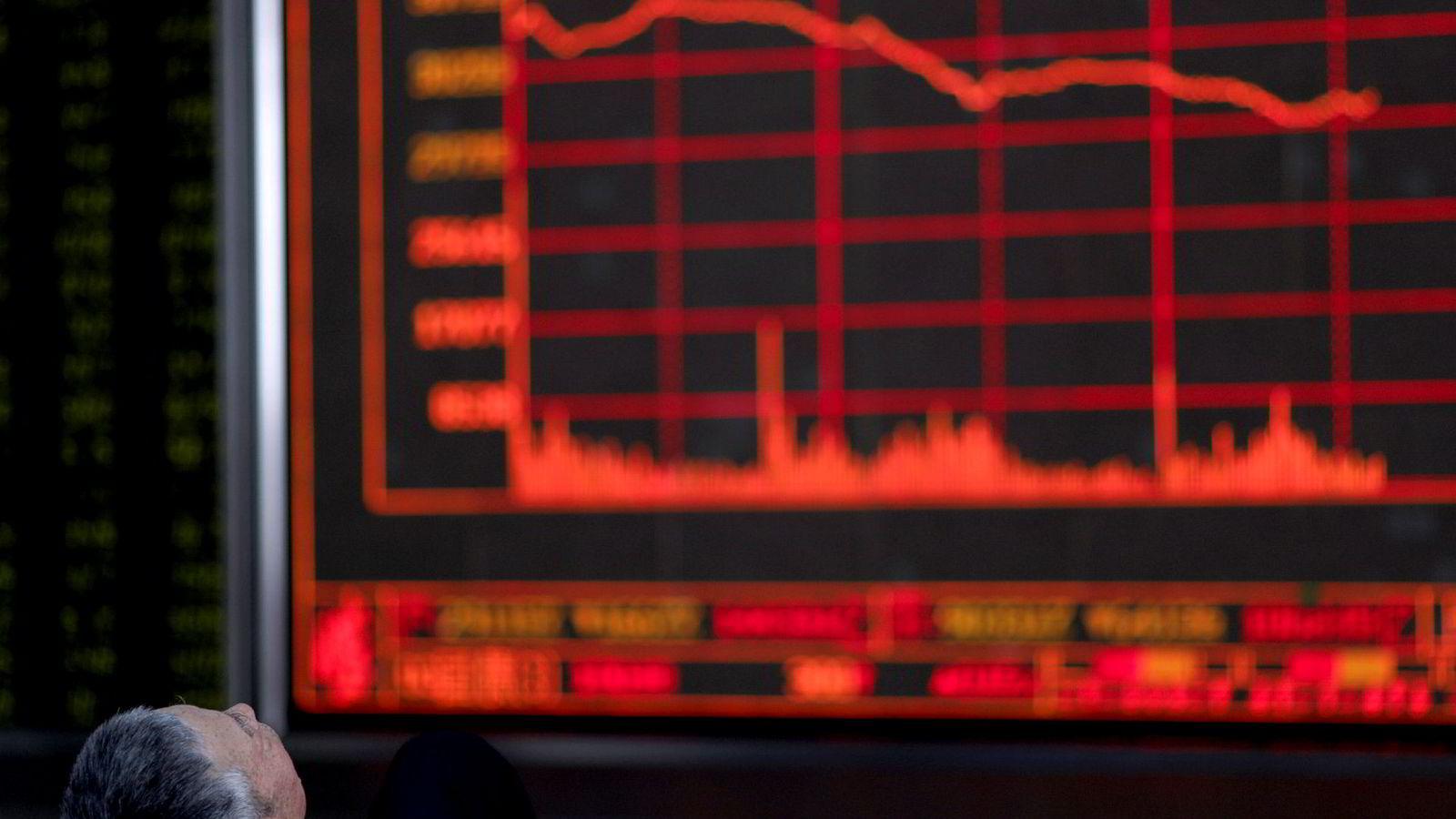 En kinesisk investor overvåker utviklingen på Shanghai-børsen fra sitt kontor i Beijing tidligere i år.
