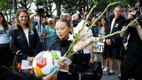 Greta Thunberg fikk blomster da hun ble møtt av tilhengere og miljøaktivister etter å ha kommet i land i New York.