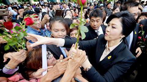 Thailands tidligere statsminister Yingluck Shinawatra mottar roser fra sine tilhengere på vei inn i retten i Bangkok tirsdag. Foto: Pornchai Kittiwongsakul, AFP/NTB Scanpix