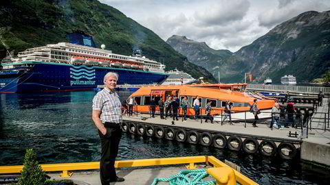 Turistsjef i destinasjon Geiranger Trollstigen, Ove Skylstad, iakttar cruisepassasjerer som skysses i land fra småbåter.