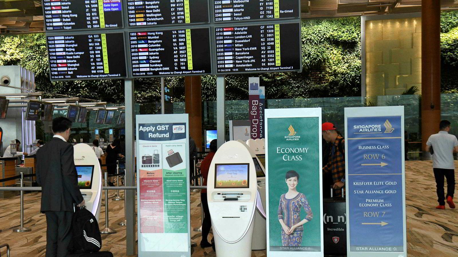 En Singapore Airlines-passasjer sjekker inn ved de automatiske innsjekkingsboksene på utenlandsterminalen ved Changi-flyplassen i Singapore torsdag 11. oktober.