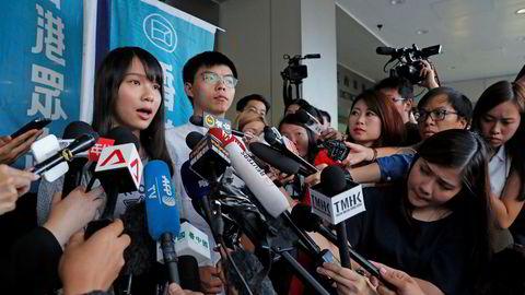 De to pro-demokrati-aktivistene Agnes Chow og Joshua Wong møtte mediene etter å ha blitt løslatt mot kausjon fredag ettermiddag i Hongkong. – Vi vil fortsette denne kampen selv om de fortsetter å arrestere og tiltale oss, sa Wong.