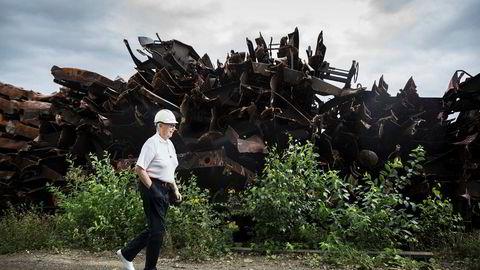 Hellik Teigen passerer gamle togvogner de hugger opp. I dag er tre generasjoner aktive i skraphandelbedriften.