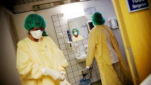 Lege Eyrund Kjetland og sykepleier Anette Schneider (ved speilet) på vei inn i et isolat på Ullevål sykehus. Foto: Linda Helen Næsfeldt
