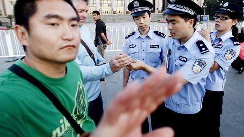 STOPP! En sivil politimann viser bort en journalist som prøver å ta bilde på Den himmelske freds plass i forbindelse med 20-årsdagen for massakren av demokratiaktivister. I dag er det 25 år siden.                    Foto: Oliver Weiken, EPA/NTB Scanpix
