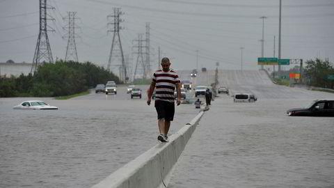 En mann balanserer mens han går langs motorveien Interstate 225 etter at orkanen Harvey rammet Texas. Det kan komme mer ekstremvær til USA om ikke lenge.