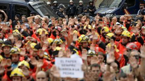 Brannmenn løfter nevene i protest mot politiets fremferd i forbindelse med søndagens folkeavstemning. Store deler av Barcelona ble lammet under tirsdagens generalstreik. Foto: Joseph Lago, AFP/NTB Scanpix