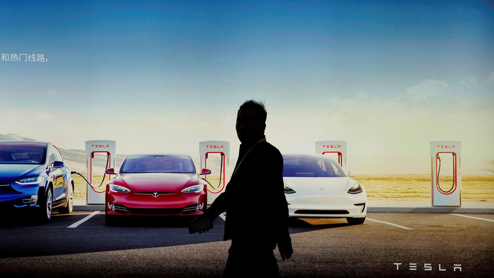En person går forbi Teslas veggreklame under bilmessen i Shanghai, Kina i april 2019.