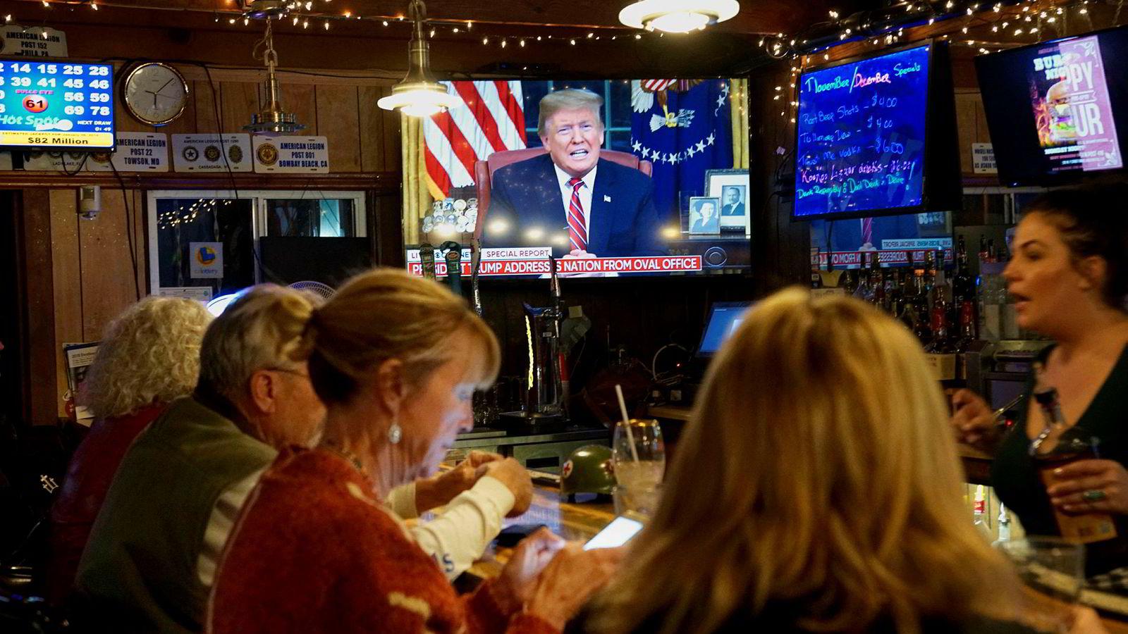 «Who blinks first?», spør amerikanske medier. President Donald Trump ønsker milliarder til å bygge mur mot Mexico. For demokratene, som har overtatt flertallet i Representantenes hus, vil det være ydmykende å bøye av for presidenten ved første konfrontasjon. Her fra en pub i Encinitas, California under talen til president Trump 8. januar.